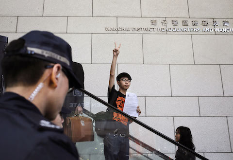 Student leader Joshua Wong flashes victory sign as he arriving at the police headquarters in Hong Kong, Friday, Jan. 16, 2015. (AP Photo/Vincent Yu)