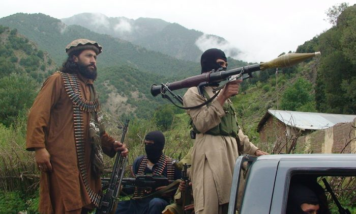 Pakistani Taliban patrol in their stronghold of Shawal in Pakistani tribal region of South Waziristan.  (AP Photo/Ishtiaq Mahsud)