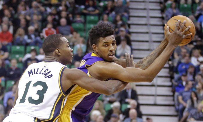 Utah Jazz guard Elijah Millsap (13) defends against Los Angeles Lakers forward Nick Young, right, in the second quarter during an NBA basketball game Friday, Jan. 16, 2015, in Salt Lake City. (AP Photo/Rick Bowmer)