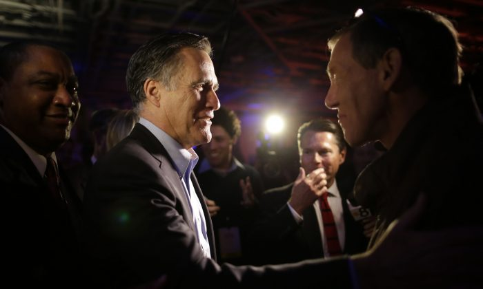 Mitt Romney, the former Republican presidential nominee, left, greets people after speaking during the Republican National Committee's winter meeting aboard the USS Midway Museum Friday, Jan. 16, 2015, in San Diego. (AP Photo/Gregory Bull)
