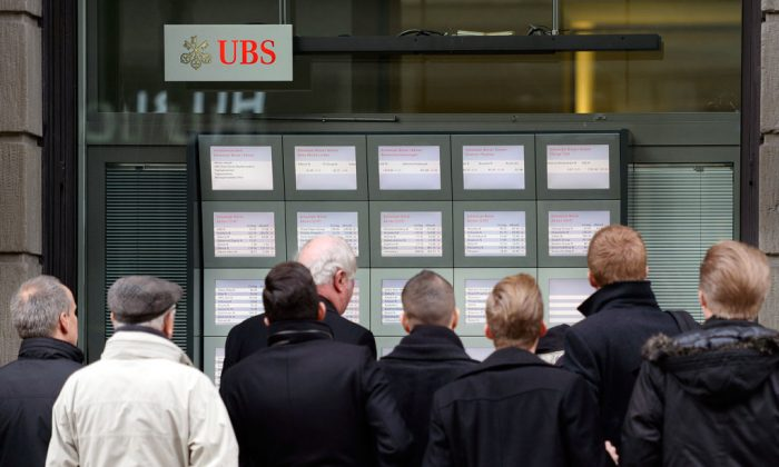 People follow the development of courses in Zurich after the turbulence at the stock exchange, pictured Thursday, Jan. 15, 2015. (AP Photo/Keystone, Walter Bieri)