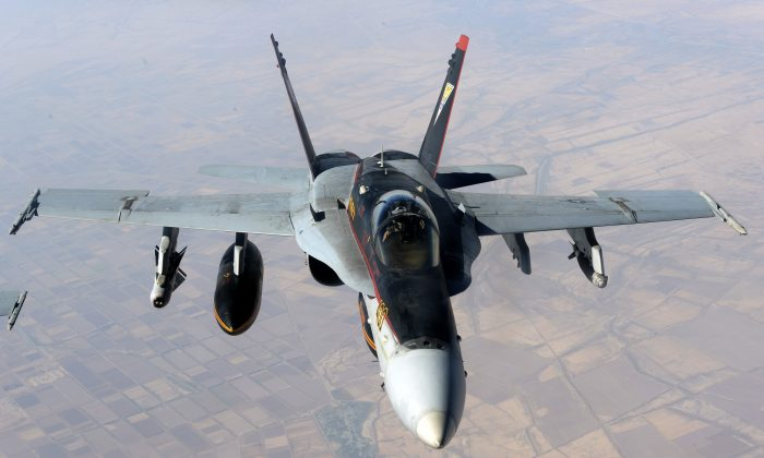A US Navy F-18E Super Hornet supporting operations against the militant Islamic State group, leaves after receiving fuel from a KC-135 Stratotanker over Iraq, on Oct. 4, 2014. US-led airstrikes and Iranian aid have helped Iraqi troops, militiamen and Kurdish fighters take back bits around Islamic State-held territory, but recapturing it all remains far out of reach for this country held hostage. (AP Photo/US Air Force, Shawn Nickel)