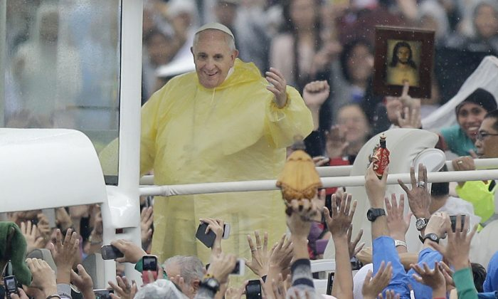Pope Francis waves the the faithful as he arrives at Rizal Park to celebrate his final Mass in Manila, Philippines, Sunday, Jan. 18, 2015. Millions filled Manila's main park and surrounding areas for Pope Francis' final Mass in the Philippines on Sunday, braving a steady rain to hear the pontiff's message of hope and consolation for the Southeast Asian country's most downtrodden and destitute. (AP Photo/Bullit Marquez)