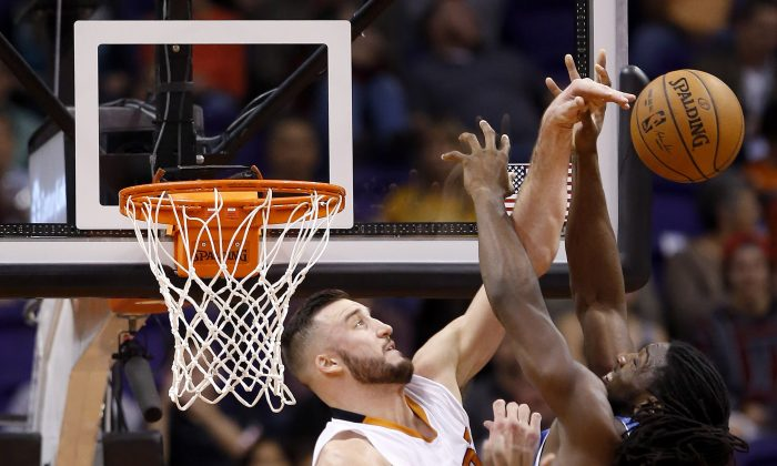 Phoenix Suns' Miles Plumlee, left, blocks the shot of Denver Nuggets' Kenneth Faried, right, during the second half of an NBA basketball game, Wednesday, Nov. 26, 2014, in Phoenix.  The Suns' Plumlee was called for a foul on the play, but the Suns defeated the Nuggets 120-112. (AP Photo/Ross D. Franklin)