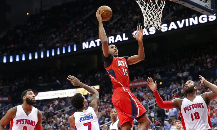 Atlanta Hawks center Al Horford (15) shoots over Detroit Pistons' Greg Monroe (10), Brandon Jennings (7) and Andre Drummond (0) in the first half of an NBA basketball game Monday, Jan. 19, 2015, in Atlanta. (AP Photo/David Tulis)