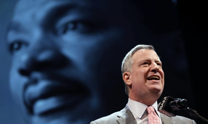 New York City Mayor Bill de Blasio speaks at a tribute to Martin Luther King, Jr. in Brooklyn, New York City, Monday, Jan. 20, 2014. At a separate Dr. King celebration in Manhattan on Monday, De Blasio invoked Dr. King's words to call for unity amid tensions between police and local residents. (AP Photo/Seth Wenig)