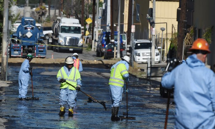 Workers clean up after an above ground oil pipeline ruptured causing some 10,000 gallons of crude oil to spill into the streets of Los Angeles on May 15, 2014. The oil was knee deep in some areas and spread over a half mile area in Atwater Village, northwest of Los Angeles. (Robyn Beck/AFP/Getty Images)