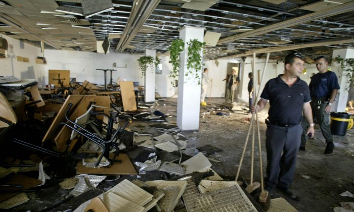 In this July 31, 2002, file photo, workers clean the inside of a cafeteria hours after a bomb exploded at Hebrew University in Jerusalem, killing nine, four of them Americans, and wounding more than 70. Terrorism victims are suing the Palestinian Liberation Organization and the Palestinian Authority in New York for damages under the Anti-Terrorism Act, which allows victims of terrorism to seek compensation through the U.S. Federal Court System. (AP Photo/David Guttenfelder, File)
