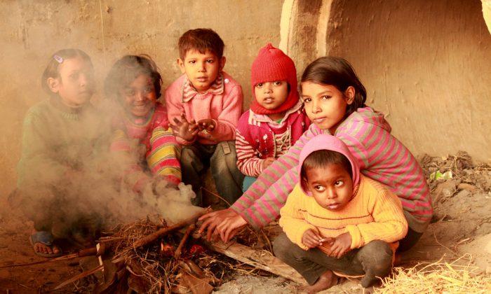 Children who live under a bridge at Akshardham, New Delhi, keep themselves warm on a cold winter day on Dec. 24, 2014. (Venus Upadhayaya/Epoch Times)