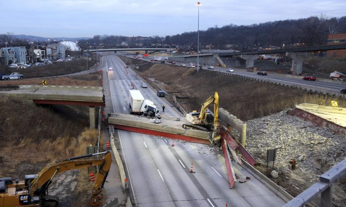 Work continues in the aftermath of the bridge collapse on Interstate 75, Tuesday, Jan. 20, 2015 in Cincinnati. The collapse killed a worker and injured a truck driver. The Ohio Department of Transportation said the busy artery through downtown Cincinnati will be closed at least two to three days. (AP Photo/The The Cincinnati Enquirer, Liz Dufour)