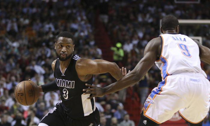 Miami Heat's Dwyane Wade (3) drives around Oklahoma City Thunder's Serge Ibaka (9) during the first half of an NBA basketball game in Miami, Tuesday, Jan. 20, 2015. (AP Photo/J Pat Carter)