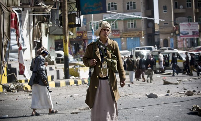 "Houthi Shiite Yemeni gather while guarding a street leading to the presidential palace in Sanaa, Yemen, Tuesday, Jan. 20, 2015. Yemen's U.S.-backed leadership came under serious threat Monday as government troops clashed with Shiite rebels near the presidential palace and a key military base in what one official called ""a step toward a coup."" (AP Photo/Hani Mohammed)"