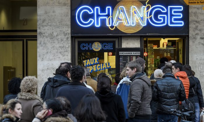 People queue at a currency exchange office in Geneva on Jan. 15, 2015. In a shock announcement on Jan. 15, Switzerland's central bank said it was ending a three-year bid to artificially hold down the value of the Swiss franc against the euro, in a move that immediately sent the safe haven currency soaring. (Fabrice Coffrini/AFP/Getty Images)