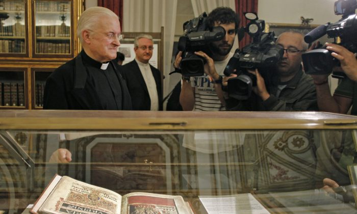 Jose Maria Diaz (R), the Dean of the Cathedral of Santiago de Compostela, poses by a replica of the 12th century religious Calixtinus Codex manuscript on display in the cathedral on July 7, 2011. A former electrician for Spain's famed cathedral in Santiago de Compostela is on trial for his alleged theft of the priceless 12th-century Codex Calixtinus religious manuscript. It is considered the first guide for Christians making the ancient pilgrimage across northern Spain called the Camino de Santiago. Jose Manuel Fernandez Castineiras appeared in court Monday Jan. 19, 2015 with his wife and son after authorities found the Codex in his garage in 2011 and recovered 1.2 million euros ($1.4 million). (AP Photo)