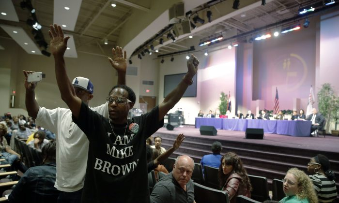 FILE - In this Sept. 9, 2014 file photo,  Marurice Brown raises his arms during a public comments portion of a meeting of the Ferguson City Council, back right, in Ferguson, Mo.  A lawsuit filed Wednesday seeks protection from a state statute that requires a name and address on political flyers. (AP Photo/Jeff Roberson, File)