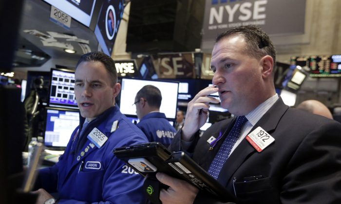 Specialist Jason Hardzewicz (L) and trader Jonathan Corpina worknon the floor of the New York Stock Exchange Wednesday, Jan. 21, 2015. The U.S. stock market is mixed in early trading after two straight days of gains. (AP Photo/Richard Drew)