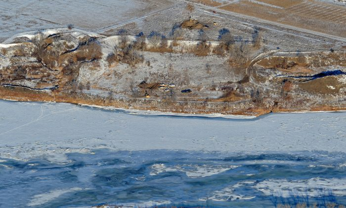 Crews work to contain an oil spill from Bridger Pipeline's broken pipeline near Glendive, Mont., in this aerial view showing both sides of the river on Monday, Jan. 19, 2015. Officials said that they were bringing truckloads of drinking water to Glendive after traces of 50,000 gallons of oil that spilled into the Yellowstone River were found in the city's water supply. (AP Photo/The Billings Gazette, Larry Mayer)