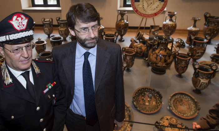 "Carabinieri Gen. Mariano Mossa (L) and Italian Culture minister Dario Franceschini pose for photographers near Antiquities recovered by Italian Carabinieri, military police, are displayed at Terme di Diocleziano museum during a press conference in Rome, Wednesday, Jan. 21, 2015. Italian authorities have unveiled what they said was a record haul of rare antiquities illegally looted from Italy and discovered during raids on Swiss warehouses belonging to an accused Sicilian art dealer. The carabinieri police's art squad estimated the value of the 5,361 vases, kraters, bronze statues and frescoes at some 50 million euros. The works, from the 8th century B.C. to the 3rd century A.D., were laid out Wednesday at the National Roman Museum and may go on public display. Carabineri Gen. Mariano Mossa said it was ""by a long shot the biggest recovery in history in terms of the quantity and quality of archaeological treasures."" They were found during an investigation into Basel-based art dealer Gianfranco Becchina, accused by prosecutors of being part of a huge trafficking network. (AP Photo/Claudio Peri, Ansa)"