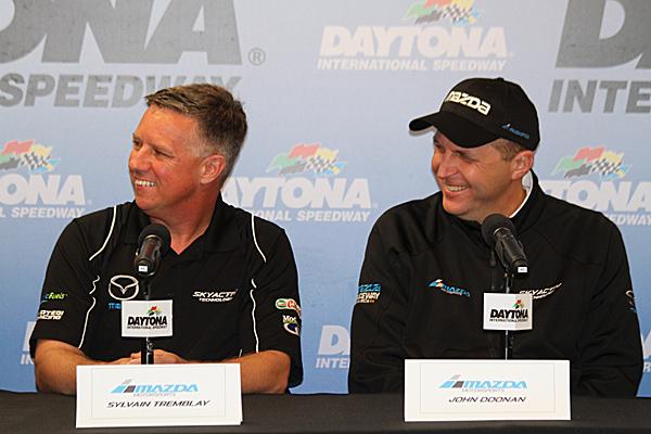 SpeedSource owner/driver Sylvain Tremblay (L) and Mazda Motorsports Director John Doonan talk about the improved 2015 Mazda diesel prototypes at the Roar Before the 24, Jan. 9 at Daytona International Speedway. (Chris Jasurek/Epoch Times)