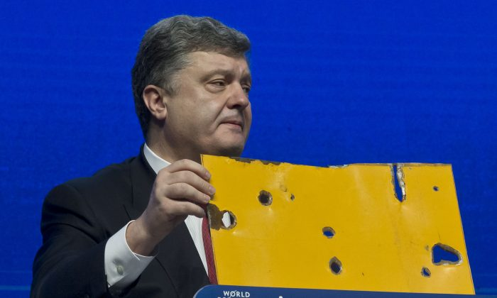 """Ukrainian President Petro Poroshenko shows a piece of a bus that was attacked recently during the panel """"The Future of Ukraine"""" in Davos, Switzerland, Wednesday, Jan. 21, 2015. The meeting runs Jan. 21 through 24 under the overarching theme """"The New Global Context"""". (AP Photo/Michel Euler)"""