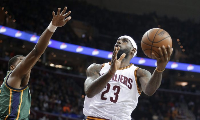 Cleveland Cavaliers' LeBron James (23) shoots against Utah Jazz's Derrick Favors during the first quarter of an NBA basketball game Wednesday, Jan. 21, 2015, in Cleveland. (AP Photo/Mark Duncan)