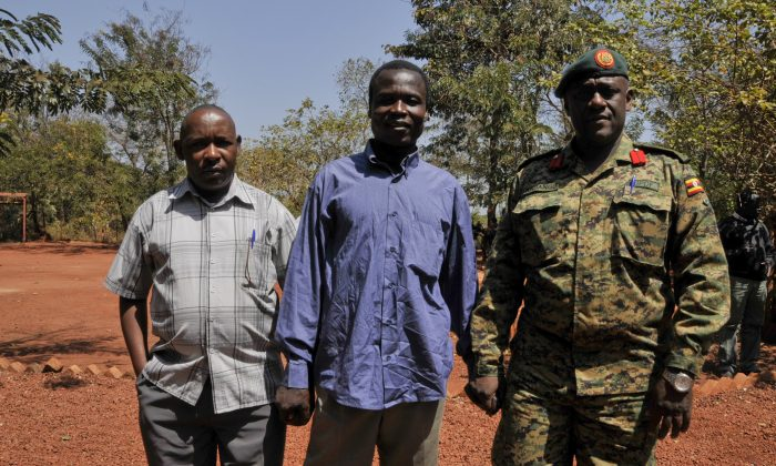 A man said by the Uganda People's Defence Force (UPDF) to be the wanted Lord's Resistance Army (LRA) commander Dominic Ongwen, center stands with Ugandan Contingent Commander to the African Union Regional Task Force Col Michael Kabango (R), and another unidentified man (L), prior to being handed over by the UPDF to the African Union Regional Task Force who later handed him over to Central African Republic authorities, in the Central African Republic, on Jan. 16, 2015. Central African Republic's Seleka rebels, who once overthrew the government, say they're entitled to a $5 million reward from the U.S. government because they say they captured and handed over the wanted international war crimes suspect Dominic Ongwen to American forces. (AP Photo/Uganda People's Defence Force, Mugisha Richard)