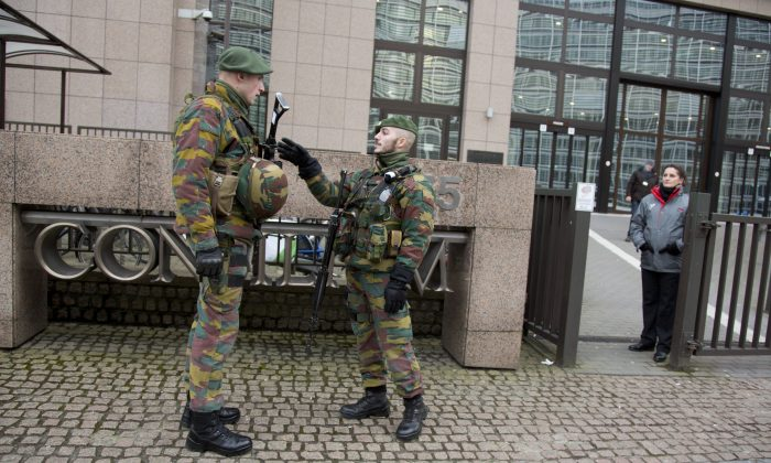 Two soldier from the Belgian military stand guard in front of EU headquarters in Brussels on Wednesday, Jan. 21, 2015. Security around Belgium has been stepped up and the military deployed to various high profile sites to guard against potential terror attacks. (AP Photo/Virginia Mayo)