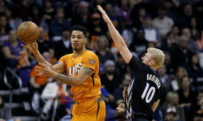Phoenix Suns' Gerald Green, left, dishes off as Minnesota Timberwolves' Chase Budinger (10) defends during the first half of an NBA basketball game, Friday, Jan. 16, 2015, in Phoenix. (AP Photo/Matt York)