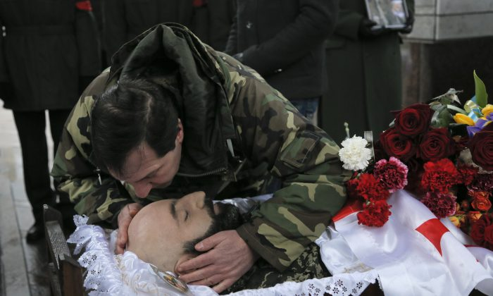 A man pays his final respect to the body of serviceman Thomas Sukhiashvili, a Georgian national who was killed in fighting against Russia-backed separatists, during a commemoration ceremony in Kiev, Ukraine, on Wednesday, Jan. 21, 2015. Sukhiashvil was a veteran of NATO-led campaigns in Afghanistan and Iraq and Georgia's 2008 war with Russia.  A former senior Georgian military official says around 100 Georgian volunteers are fighting alongside Ukrainian forces in the conflict against Russian-backed separatists. (AP Photo/Efrem Lukatsky)