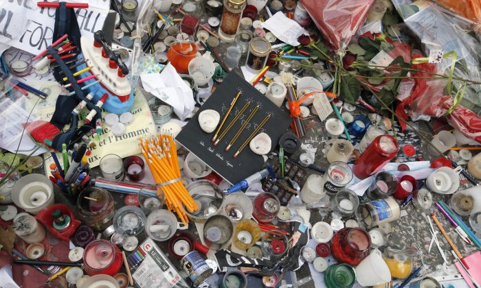 All kinds of tributes including candles and pencils are displayed on the pavement close to the Charlie Hebdo site where brothers, Said and Cherif Kouachi killed people in a terror attack at the offices of French satirical publication Charlie Hebdo, in Paris, Tuesday Jan. 20, 2015. Brothers, Said and Cherif Kouachi and their friend, Amedy Coulibaly, killed 17 people at the satirical newspaper Charlie Hebdo, a kosher grocery and elsewhere last week. (AP Photo/Francois Mori)