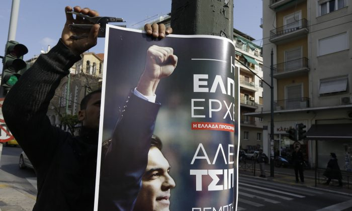 An Egyptian worker displays a poster on an electricity pole promoting Alexis Tsipras, head of Greece's Syriza left-wing main opposition party, pre-election speech in Athens on Jan. 21, 2015. His left-wing Syriza party is poised to win a general election in Greece Sunday, a landmark event for Europe's ambitious political newcomers with domestic resonance in a country with a long history of deadly political division that has recently been ravaged by financial crisis. (AP Photo/Thanassis Stavrakis)