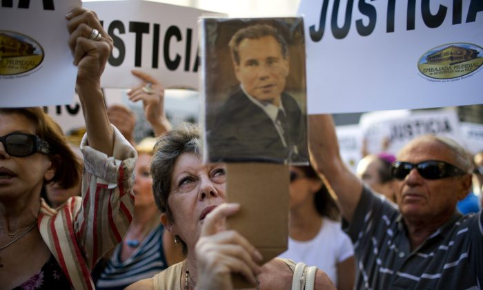 A woman chants the Argentine national anthem holding a portrait of the late prosecutor Alberto Nisman outside the AMIA Jewish community center in Buenos Aires, Argentina, Wednesday, Jan. 21, 2015. Nisman, who had been investigating the 1994 bombing of the Jewish community center that killed 85 people and who accused President Cristina Fernandez of shielding Iranian suspects, was found dead from a gunshot to the head, in his apartment late Sunday, hours before he was to testify in a Congressional hearing about the case. (AP Photo/Rodrigo Abd)