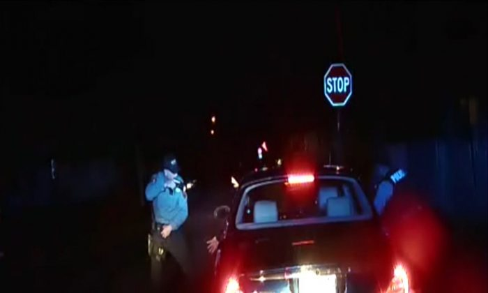In this frame grab from an officer's dashboard camera taken Dec. 30, 2014, and provided by the Bridgeton, N.J. Police Department, police officers Braheme Days and Roger Worley stand near a car they pulled over for running a stop sign in Bridgeton. One of the officers warned his partner that he could see a gun in the glove compartment. The nearly two-minute standoff resulted in the death of Jerame Reid, one of two men in the car. (AP Photo/Bridgeton Police Department)