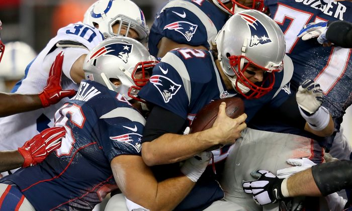 Tom Brady of the New England Patriots (C with the football) at the 2015 AFC Championship Game in Foxboro, Mass., on Jan. 18. The Patriots have been accused of using underinflated footballs.  (Jim Rogash/Getty Images)