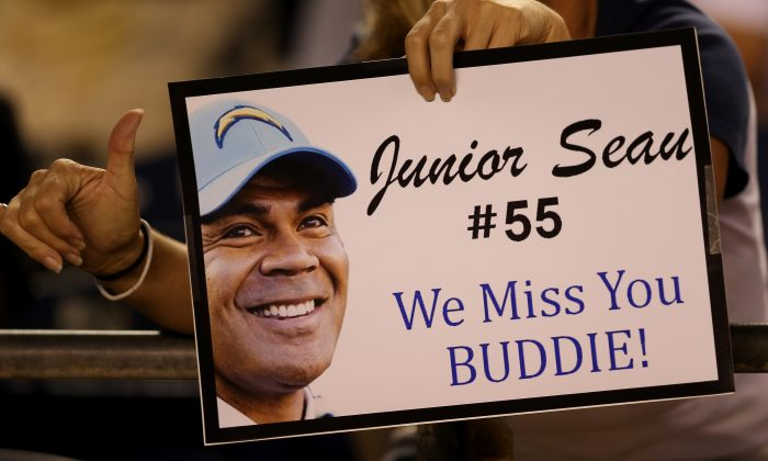 A fan holds up a sign honoring late San Diego Chargers linebacker Junior Seau during the game against the Green Bay Packers in San Diego on Aug. 9, 2012. (Stephen Dunn/Getty Images)