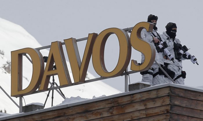 Armed Swiss police officers stand guard on the roof of a hotel, the day before the opening of the annual meeting of the World Economic Forum in Davos, Switzerland, Tuesday, Jan. 20, 2015. The world's financial and political elite will head this week to the Swiss Alps for 2015's gathering of the World Economic Forum at the Swiss ski resort of Davos. (AP Photo/Michel Euler)