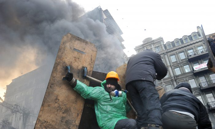 Anti-government protesters take cover under makeshift shields during clash with riot police in Kyiv on Jan. 25, 2014. (Genya Savilov/AFP/Getty Images)