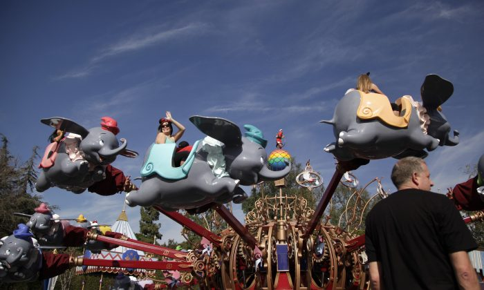 Visitors ride Dumbo the Flying Elephant at Disneyland, Thursday, Jan. 22, 2015, in Anaheim, Calif. Seventy people have been infected in a measles outbreak that led California public health officials to urge those who haven't been vaccinated against the disease, including children too young to be immunized, should avoid Disney parks where the spread originated. (AP Photo/Jae C. Hong)