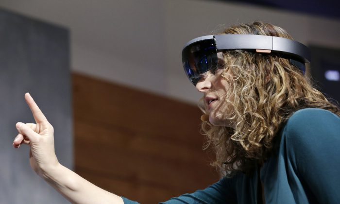 Microsoft's Lorraine Bardeen demonstrates HoloLens headset during an event at the company's headquarters in Redmond, Wash., on Jan. 21, 2015. (AP Photo/Elaine Thompson)