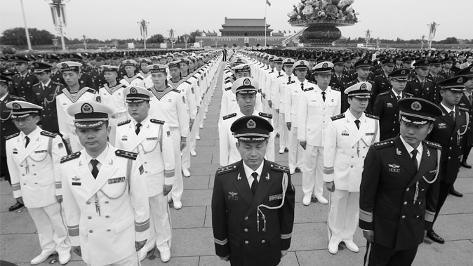 Chinese military officers and soldiers stand in Beijing's Tiananmen Square on Sept. 30, 2014. A long-lasting system of corruption has allowed China's military officers to profit from the black market and human rights abuses. (STR/AFP/Getty Images)