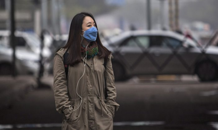A foreign tourist wears a mask to protect herself from pollutants while walking on a sideway in New Delhi, India on, Jan. 23, 2015. Hazy skies served as the backdrop to meetings with Indian Prime Minister Narendra Modi and other officials who discussed India's biggest environmental woes. (AP Photo/Tsering Topgyal)