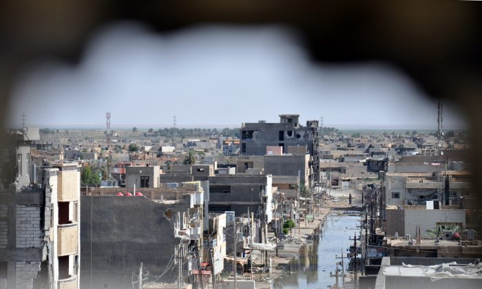 A picture taken through a hole in a wall on June 24, 2014 in the city of Ramadi in the Anbar province, shows buildings that were damaged during fighting between government forces including fighters of the Sunni anti-Al-Qaeda militia Sahwa (Awakening) and anti-government militants, including those from the jihadist Islamic State of Iraq and the Levant (ISIL). (AFP/Getty Images)