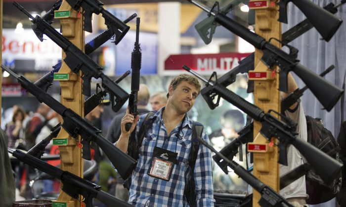 A man looks at a display of rifles at the Rock River Arms booth during the 35th annual SHOT Show in Las Vegas on Jan. 17, 2013.   (AP Photo/Julie Jacobson)