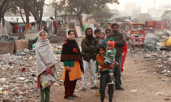 Residents of a slum in the Kanega locality of Gurgaon city in Delhi on Jan. 15, 2015. They have no toilets and have to defecate in a open dump of garbage and construction waste nearby. (Venus Upadhayaya/Epoch Times)
