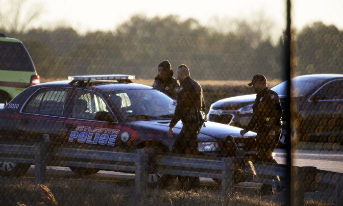 """Police officers leave a fire station off the tarmac at at Hartsfield-Jackson Atlanta International Airport where two airplanes were being searched after authorities received what they described as """"credible"""" bomb threats, Saturday, Jan. 24, 2015, in Atlanta. (AP Photo/David Goldman)"""