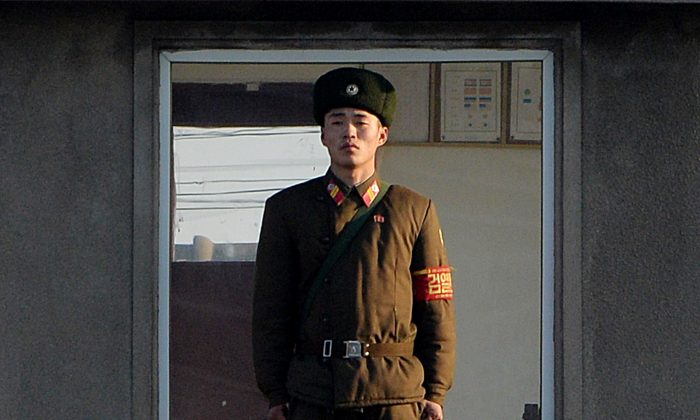 A North Korea soldier stands guard on the banks of the Yalu River which separates the North Korean town of Sinuiju from the Chinese border town of Dandong on Dec. 17, 2013. On Dec. 27, 2014 a North Korean soldier crossed the border into China and killed four Chinese villagers, apparently while seeking food. (Mark Ralston/AFP/Getty Images)