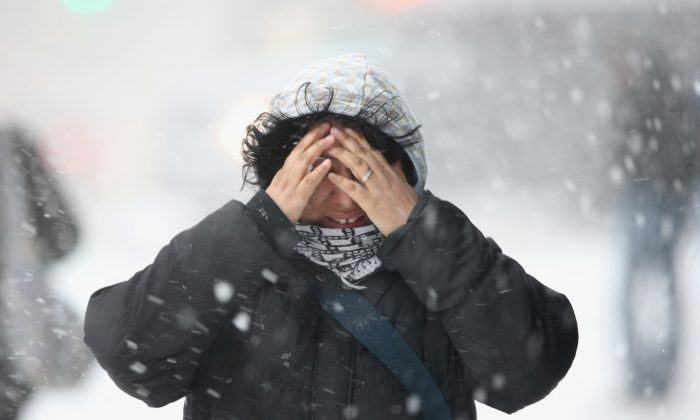 A woman covers her face while walking through the snow in New York City on Feb. 13. New York is expecting up to 3 feet of snow by late night, Jan. 27, 2015. (John Moore/Getty Images)