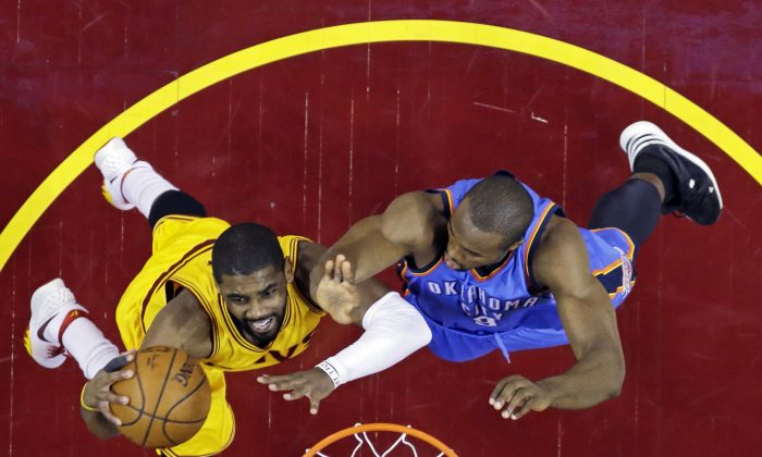 Cleveland Cavaliers' Kyrie Irving, left, shoots against Oklahoma City Thunder's Serge Ibaka, from Congo, in the first half of an NBA basketball game Sunday, Jan. 25, 2015, in Cleveland. (AP Photo/Mark Duncan)