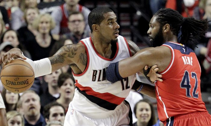 Portland Trail Blazers forward LaMarcus Aldridge, left, works the ball in against Washington Wizards center Nene during the first half of an NBA basketball game in Portland, Ore., Saturday, Jan. 24, 2015.  (AP Photo/Don Ryan)