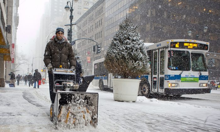 A man plowing on a street in Manhattan, New York City, on Jan. 21, 2014. A winter storm bringing up to two feet of snow will descend upon New York City and the Northeastern region Monday until Wednesday. (Samira Bouaou/Epoch Times)